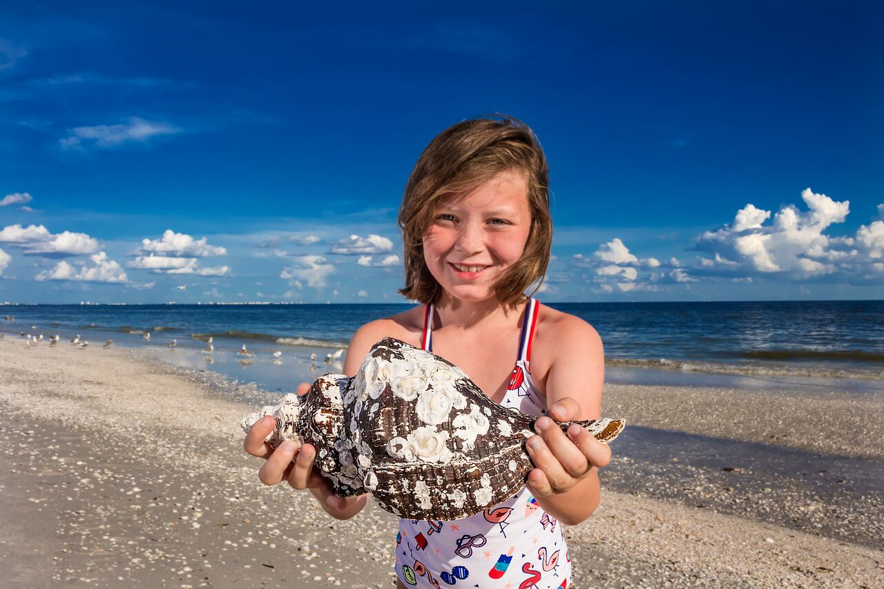 girl holding horse conch on beach sanibel